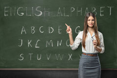 Attractive young woman teacher in a classroom. Teaching the English language with a hand written alphabet on the chalkboard royalty free stock photo