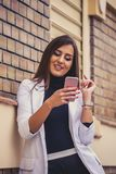 Attractive young woman texting on her mobile phone. With a smile as she stands in front of a brick wall. Checking email via mobile phone Royalty Free Stock Images