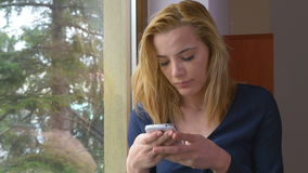 Attractive young woman texting on a smartphone at the window stock video