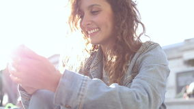 Attractive young woman texting and smiling on her smart phone outdoors stock footage