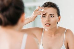 Attractive young woman touching forehead and looking at mirror. In bathroom royalty free stock photo