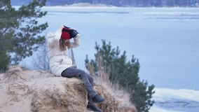 Attractive young woman tourist in a red hat sits in a on the shore and enjoys a virtual reality helmet. 4k Stock Image
