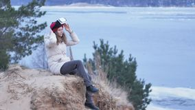 Attractive young woman tourist in a red hat sits in a on the shore and enjoys a virtual reality helmet. 4k Stock Images