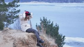 Attractive young woman tourist in a red hat sits in a on the shore and enjoys a virtual reality helmet. 4k Royalty Free Stock Photo