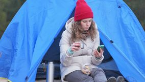 Attractive young woman tourist in a red hat sits in a tourist tent and drinks tea from a thermos. 4k Stock Image