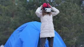 Attractive young woman tourist in a red hat sits in a tourist tent and enjoys a virtual reality helmet. 4k stock video