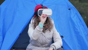 Attractive young woman tourist in a red hat sits in a tourist tent and enjoys a virtual reality helmet. 4k Stock Images