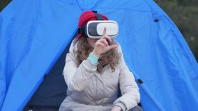 Attractive young woman tourist in a red hat sits in a tourist tent and enjoys a virtual reality helmet. 4k Stock Image
