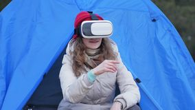 Attractive young woman tourist in a red hat sits in a tourist tent and enjoys a virtual reality helmet. 4k Stock Photography