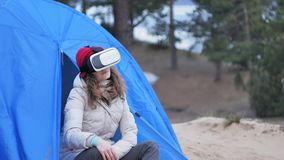 Attractive young woman tourist in a red hat sits in a tourist tent and enjoys a virtual reality helmet. 4k Royalty Free Stock Images