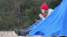 Attractive young woman tourist in a red hat sits in a tourist tent and drinks tea from a thermos. 4k Stock Images