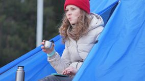 Attractive young woman tourist in a red hat sits in a tourist tent and drinks tea from a thermos. 4k Royalty Free Stock Photos