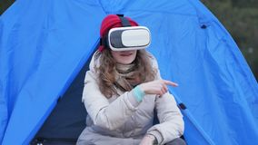 Attractive young woman tourist in a red hat sits in a tourist tent and enjoys a virtual reality helmet. 4k Royalty Free Stock Photo