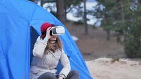 Attractive young woman tourist in a red hat sits in a tourist tent and enjoys a virtual reality helmet. 4k Stock Photos