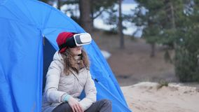 Attractive young woman tourist in a red hat sits in a tourist tent and enjoys a virtual reality helmet. 4k Royalty Free Stock Photos
