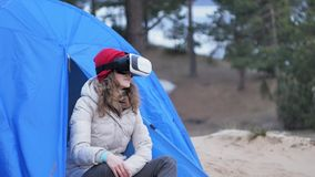 Attractive young woman tourist in a red hat sits in a tourist tent and enjoys a virtual reality helmet. 4k Stock Photo