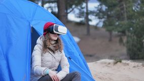 Attractive young woman tourist in a red hat sits in a tourist tent and enjoys a virtual reality helmet. 4k Royalty Free Stock Photography