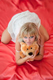 Attractive young woman with toy on a bed Royalty Free Stock Image