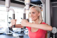 Attractive young woman is training in fitness. Beautiful fit girl is exercising with the equipment in gym. She is standing and smiling. The lady is looking Royalty Free Stock Photography