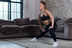 Attractive young woman training indoors doing side lunges working out legs, hips and buttocks royalty free stock photos