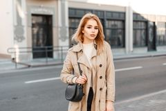 Attractive young woman in trendy spring coat in white t-shirt with stylish black leather handbag posing in the city outside. European stylish girl model royalty free stock photo