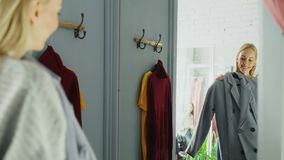 Attractive young woman is trying elegant coat while standing in fitting room is clothing boutique. She is looking at. Herself in large mirror, slightly turning stock footage