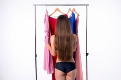 Attractive young woman trying to choose dress. Isolated on white.  Royalty Free Stock Photography