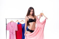 Attractive young woman trying to choose dress. Isolated on white.  Royalty Free Stock Photos