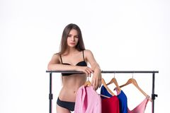 Attractive young woman trying to choose dress. Isolated on white.  Stock Photo