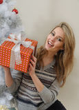 An attractive young woman trying to figure out the gift she rece Royalty Free Stock Photo