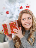 An attractive young woman trying to figure out her gift for Chri Stock Images