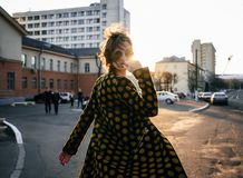 Attractive young woman turns around at camera on street at sunset. Attractive young woman with wind disheveled hair wearing polka dot coat and fashion sunglasses royalty free stock photos