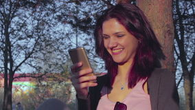 Attractive young woman typing a message on her phone stock footage