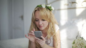 Attractive young woman using app on smartphone in the bedroom. Steadicam shot stock video