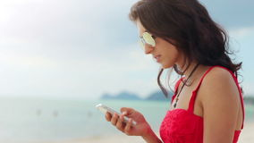 Attractive young woman using her phone on the beach stock video footage