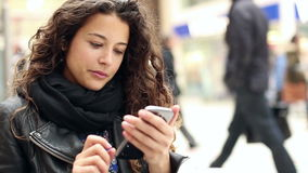 Attractive young woman using her smart phone. Young and attractive woman using her smart phone and smiling