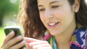 Attractive young woman using her touch screen phone in a park stock video