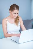 Attractive young woman using a laptop at home Royalty Free Stock Photography