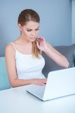Attractive young woman using a laptop at home Royalty Free Stock Photo