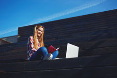 Attractive young woman using laptop sitting on wooden staircase enjoying sunny day outdoors Stock Image