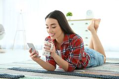 Attractive young woman using mobile phone. While drinking coffee at home Royalty Free Stock Image