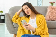 Attractive young woman using mobile phone near sofa. At home Royalty Free Stock Photography