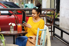 Attractive young woman using mobile phone at outdoor cafe Stock Photo