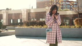 Attractive young woman using smartphone in the city, dressed in coat and hat. young woman is texting a message on the. Attractive young woman using smartphone in stock footage
