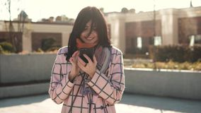 Attractive young woman using smartphone in the city, dressed in coat and hat. young woman is reading a message on the. Attractive young woman using smartphone in stock video footage