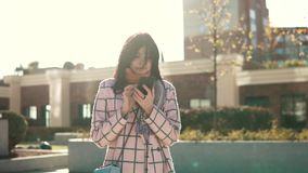 Attractive young woman using smartphone in the city, dressed in coat and hat. young woman is texting a message on the. Attractive young woman using smartphone in stock video