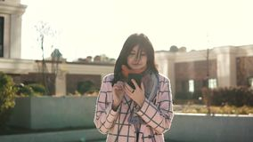 Attractive young woman using smartphone in the city, dressed in coat and hat. young woman is reading a message on the. Attractive young woman using smartphone in stock footage