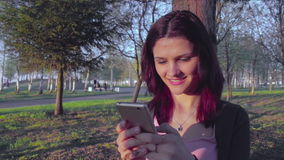 Attractive young woman using smartphone outdoors stock footage