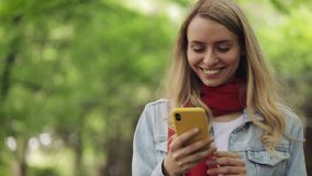 Attractive young woman using smartphone walking down the park. Spring or summer time. stock video