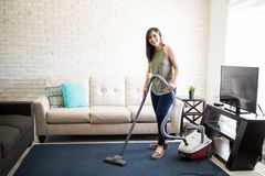 Cheerful young housewife cleaning blue carpet. Attractive young woman using vacuum cleaner to clean home while looking at camera Stock Photography